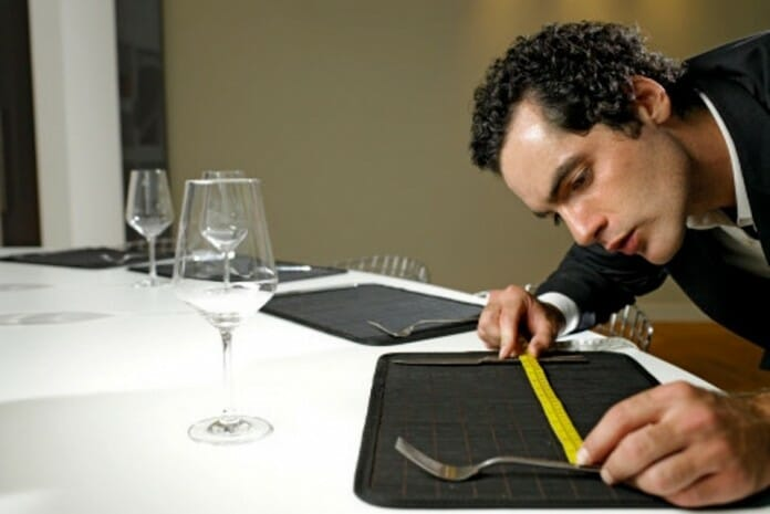 Young man measuring space between cutlery on dinner table, close-up
