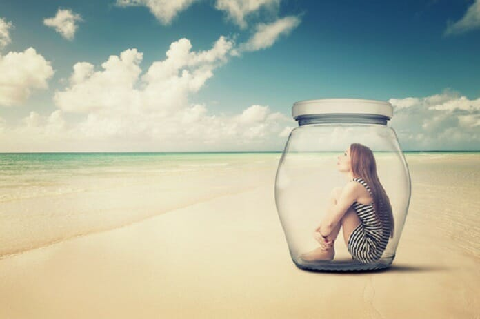 photodune  woman sitting in a glass jar on a beach looking at the ocean views