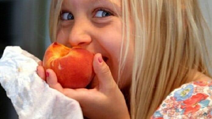 Girl eating peach
